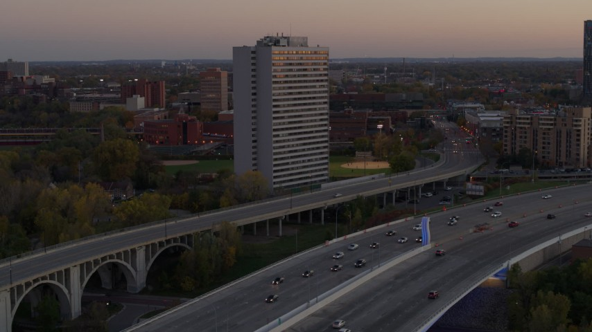 5.7K stock footage aerial video of reverse view of a condo complex beside a bridge at sunset, Minneapolis, Minnesota Aerial Stock Footage | DX0001_002549