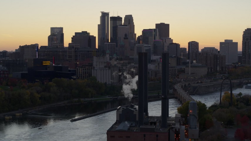 5.7K stock footage aerial video flyby power plant and river to focus on skyline at sunset, Downtown Minneapolis, Minnesota Aerial Stock Footage | DX0001_002552