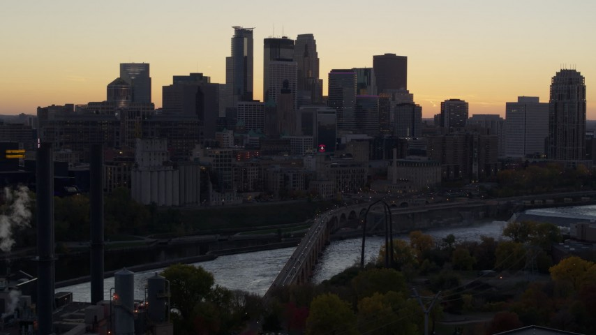 5.7K stock footage aerial video of the city's skyline, bridge and the river at sunset, reveal power plant, Downtown Minneapolis, Minnesota Aerial Stock Footage | DX0001_002555
