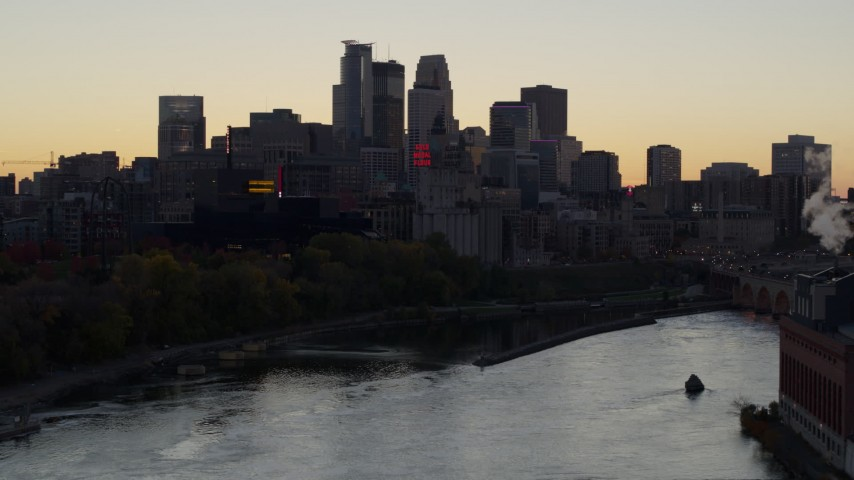 5.7K stock footage aerial video of the city's skyline across the river at sunset, seen during ascent, Downtown Minneapolis, Minnesota Aerial Stock Footage | DX0001_002556