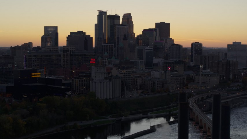 5.7K stock footage aerial video of the city's skyline across the river at sunset, reveal a bridge, Downtown Minneapolis, Minnesota Aerial Stock Footage | DX0001_002557