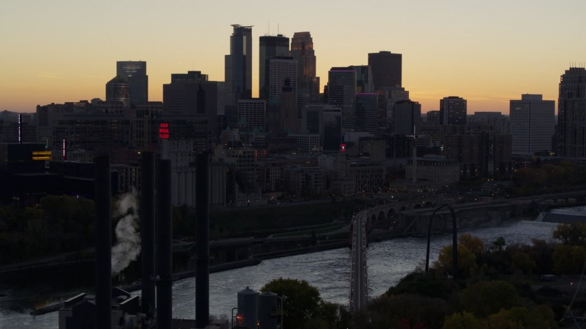 5.7K stock footage aerial video of the city's skyline and river bridge at sunset, seen from power plant, Downtown Minneapolis, Minnesota Aerial Stock Footage | DX0001_002558
