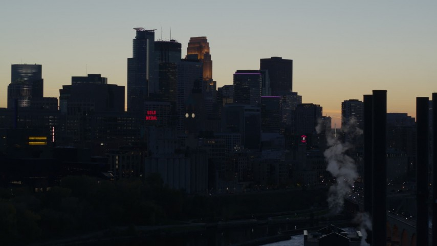 5.7K stock footage aerial video flyby smoke stacks with view of the city skyline at twilight, Downtown Minneapolis, Minnesota Aerial Stock Footage | DX0001_002559