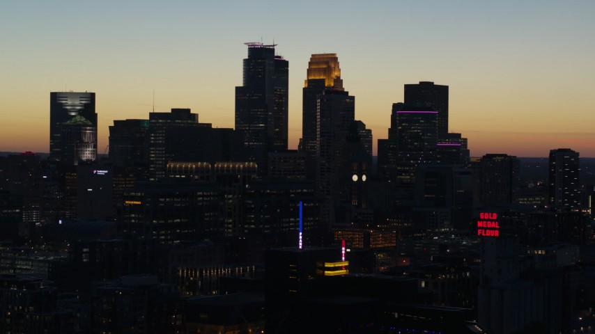 5.7K stock footage aerial video passing skyscrapers lit for night in the city skyline at twilight, Downtown Minneapolis, Minnesota Aerial Stock Footage | DX0001_002577