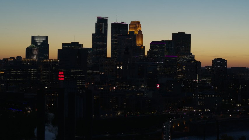 5.7K stock footage aerial video flying by the city skyline lit for the night at twilight, Downtown Minneapolis, Minnesota Aerial Stock Footage | DX0001_002580
