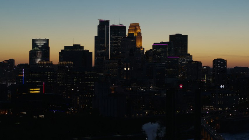 5.7K stock footage aerial video ascend by the city skyline lit for the night at twilight, Downtown Minneapolis, Minnesota Aerial Stock Footage | DX0001_002581