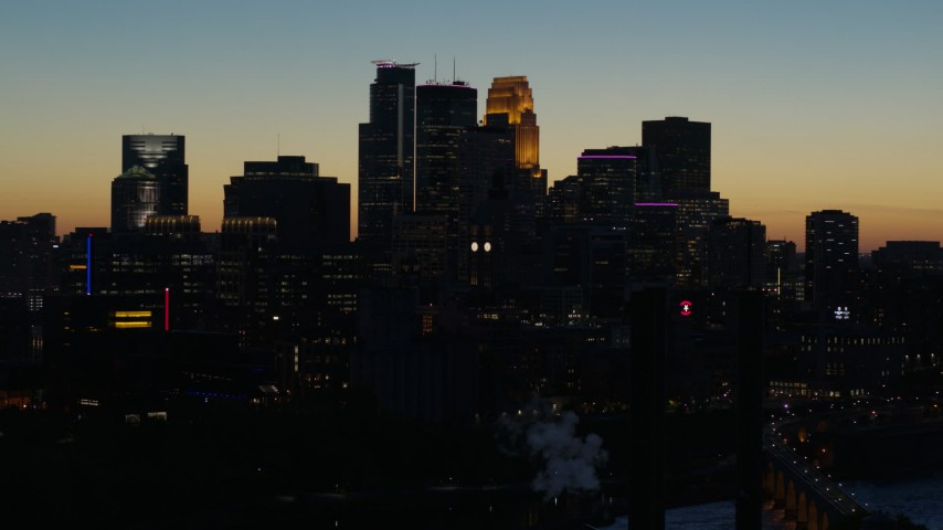 5.7K stock footage aerial video descend by the city skyline lit for the night at twilight, Downtown Minneapolis, Minnesota Aerial Stock Footage | DX0001_002582