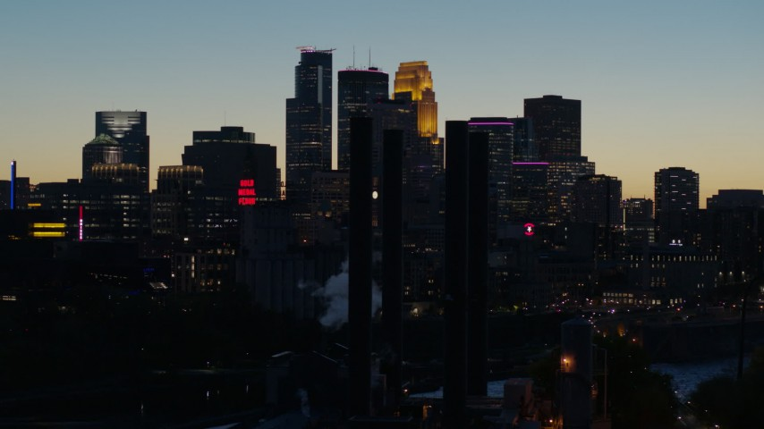 5.7K stock footage aerial video flyby smoke stacks and the city skyline lit for the night at twilight, Downtown Minneapolis, Minnesota Aerial Stock Footage DX0001_002583 | Axiom Images