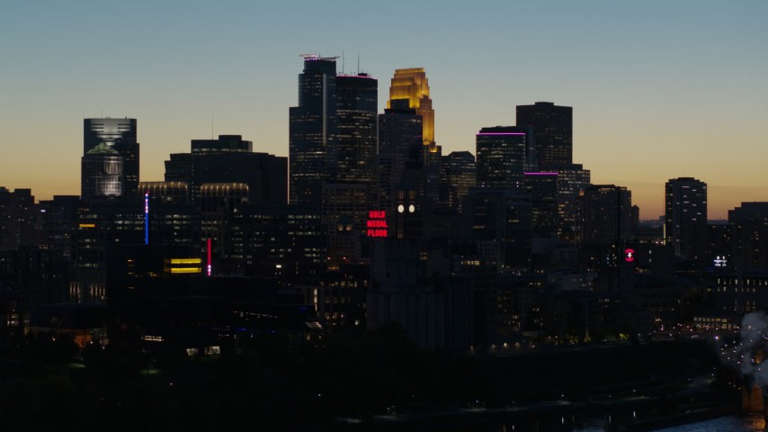 5.7K stock footage aerial video pass by smoke stacks and the city skyline lit for the night at twilight, Downtown Minneapolis, Minnesota Aerial Stock Footage | DX0001_002584