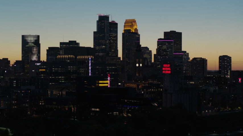5.7K stock footage aerial video descend and flyby the city skyline lit for the night at twilight, Downtown Minneapolis, Minnesota Aerial Stock Footage | DX0001_002585