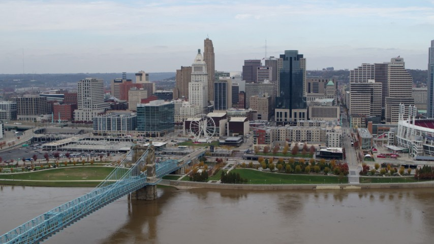 5.7K aerial video of a reverse view of the city skyline and bridge by Ohio River, Downtown Cincinnati, Ohio Aerial Stock Footage | DX0001_002598