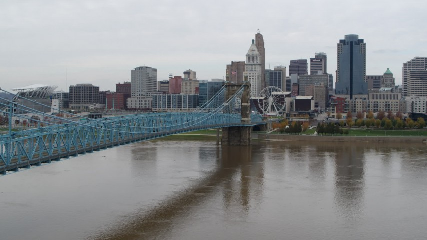 5.7K stock footage aerial video descend near the Roebling Bridge spanning Ohio River near the city skyline, Downtown Cincinnati, Ohio Aerial Stock Footage | DX0001_002640