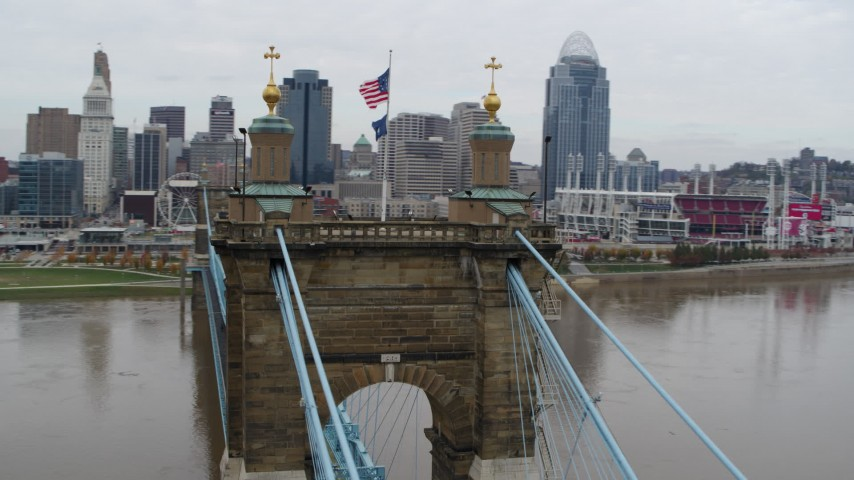 5.7K aerial video orbit flags on top of the Roebling Bridge, with view of the city skyline, Downtown Cincinnati, Ohio Aerial Stock Footage | DX0001_002643