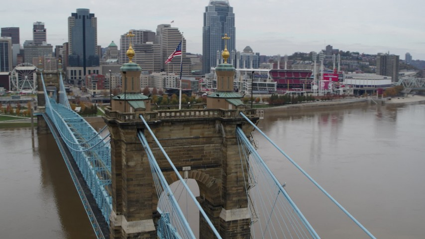 5.7K stock footage aerial video orbit flags on top of the Roebling Bridge, reveal the city skyline, Downtown Cincinnati, Ohio Aerial Stock Footage | DX0001_002644