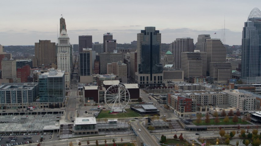 5.7K aerial video of flying by tall skyscrapers and skyline near Ferris wheel in Downtown Cincinnati, Ohio Aerial Stock Footage | DX0001_002670