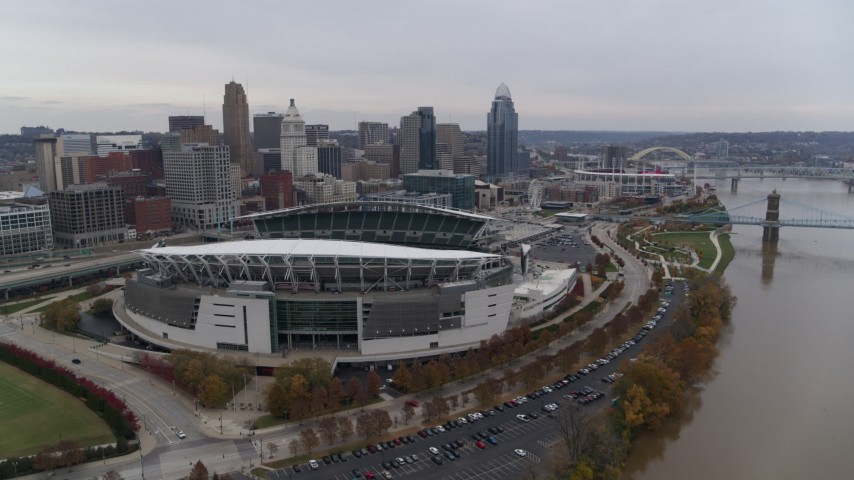 5.7K aerial video reverse view of football stadium and skyline, reveal Ohio River in Downtown Cincinnati, Ohio Aerial Stock Footage | DX0001_002682