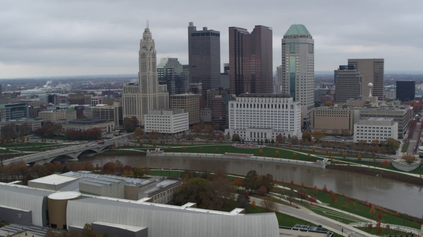 5.7K aerial video of flying by the city's skyline across the Scioto River, Downtown Columbus, Ohio Aerial Stock Footage DX0001_002718