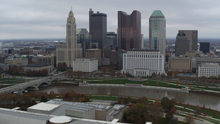 5.7K aerial video of passing by the city's skyline across the Scioto River, Downtown Columbus, Ohio Aerial Stock Footage | DX0001_002719