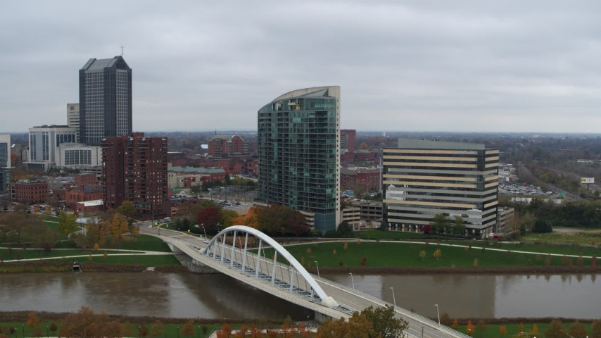 5.7K aerial video ascend by riverfront condo complex and office building by bridge and river, Downtown Columbus, Ohio Aerial Stock Footage DX0001_002735