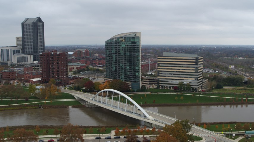 5.7K stock footage aerial video reverse view of riverfront condo complex and office building by bridge and river, Downtown Columbus, Ohio Aerial Stock Footage | DX0001_002736