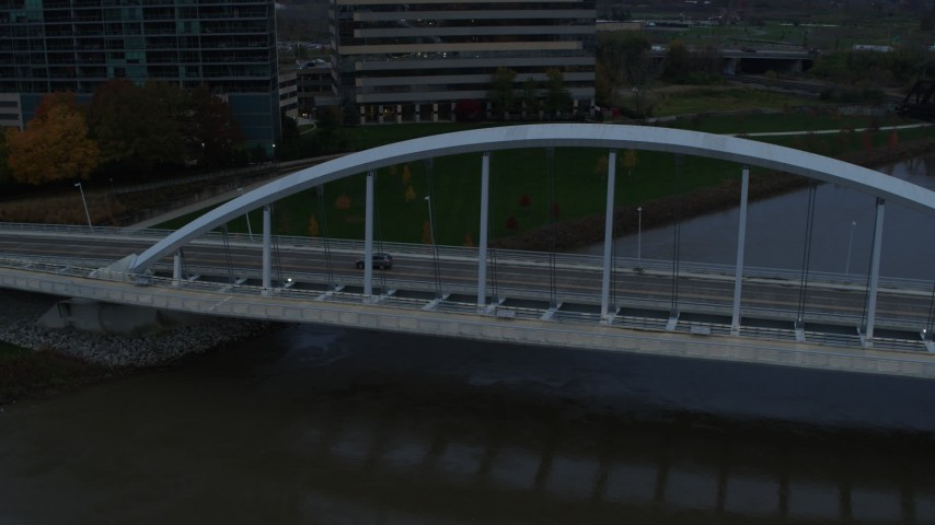 5.7K aerial video reverse view of the Main Street Bridge spanning the Scioto River at sunset, Downtown Columbus, Ohio Aerial Stock Footage | DX0001_002738