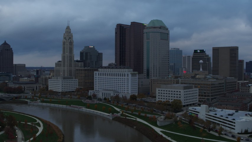 5.7K aerial video reverse view of city skyline on the other side of the Scioto River at sunset, Downtown Columbus, Ohio Aerial Stock Footage | DX0001_002740