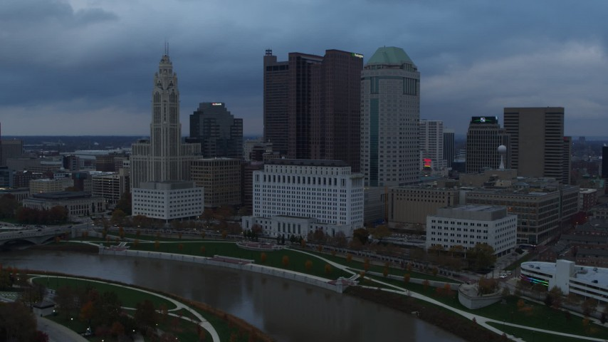5.7K stock footage aerial video fly away from and by city skyline by the Scioto River at sunset, Downtown Columbus, Ohio Aerial Stock Footage | DX0001_002742