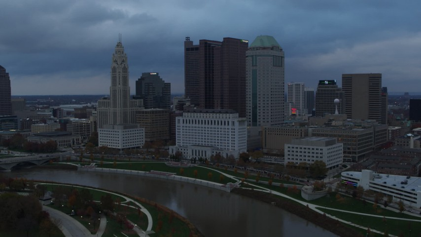 5.7K aerial video fly by and away from the city skyline by the Scioto River at sunset, Downtown Columbus, Ohio Aerial Stock Footage | DX0001_002743
