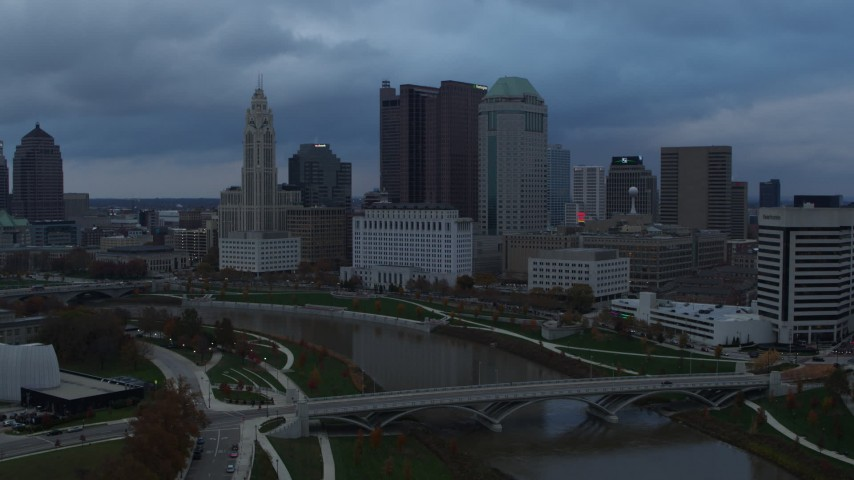 5.7K stock footage aerial video descend with view of bridge and city skyline by the Scioto River at sunset, Downtown Columbus, Ohio Aerial Stock Footage | DX0001_002744