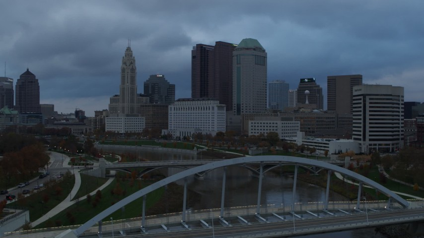 5.7K stock footage aerial video of the city skyline seen from bridge spanning the Scioto River at sunset, Downtown Columbus, Ohio Aerial Stock Footage | DX0001_002745