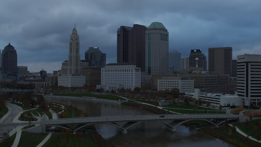 5.7K aerial video approach the city skyline from bridges spanning the Scioto River at sunset, Downtown Columbus, Ohio Aerial Stock Footage | DX0001_002746