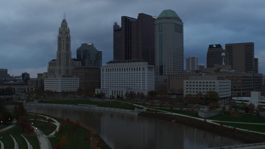 5.7K aerial video flyby the city skyline and the Scioto River at sunset during descent, Downtown Columbus, Ohio Aerial Stock Footage | DX0001_002748