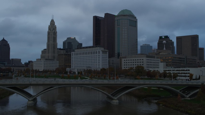 5.7K aerial video ascend from bridge for view of the city skyline and the Scioto River at sunset, Downtown Columbus, Ohio Aerial Stock Footage | DX0001_002749