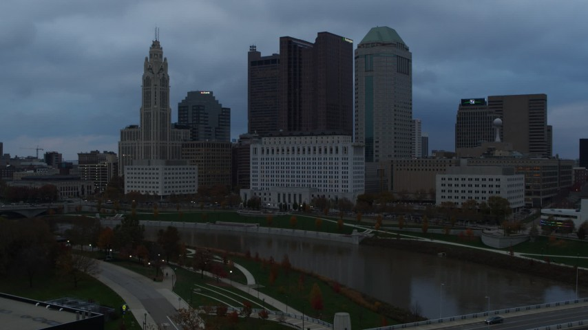 5.7K stock footage aerial video flying by the city skyline and the Scioto River at sunset, descend to reveal bridge, Downtown Columbus, Ohio Aerial Stock Footage | DX0001_002751