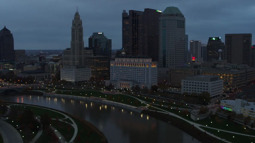 5.7K aerial video of flying by the city skyline and the Scioto River at sunset, Downtown Columbus, Ohio Aerial Stock Footage | DX0001_002754