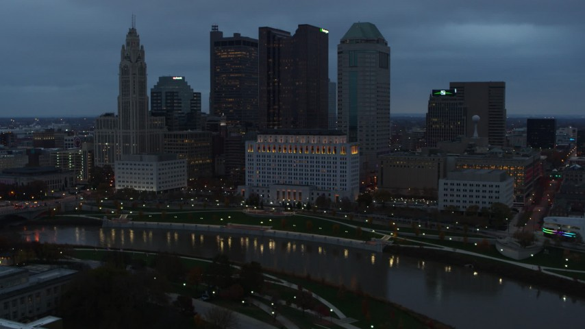 5.7K stock footage aerial video of flying by Scioto River and then approach city skyline at sunset, Downtown Columbus, Ohio Aerial Stock Footage | DX0001_002755