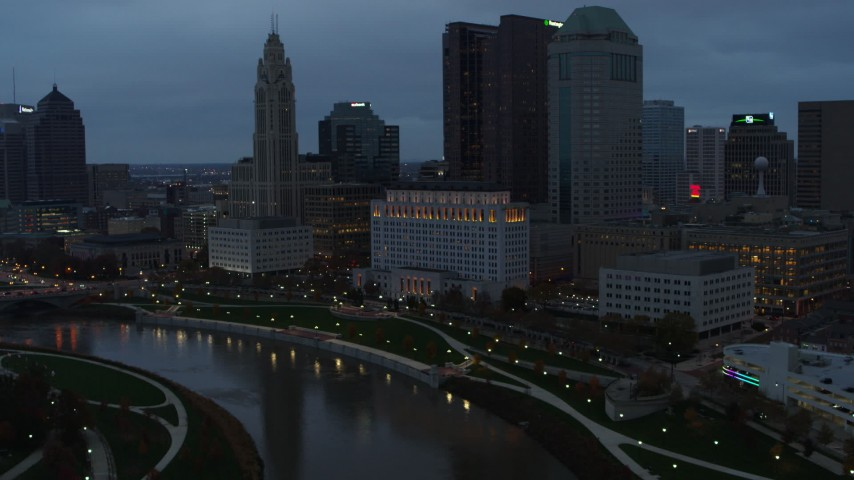 5.7K aerial video of flying by Scioto River and city skyline at sunset, Downtown Columbus, Ohio Aerial Stock Footage | DX0001_002756