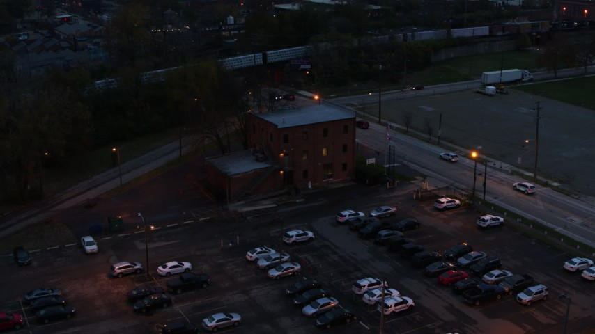 5.7K aerial video of a reverse view of a brick police station at twilight in Columbus, Ohio Aerial Stock Footage | DX0001_002763