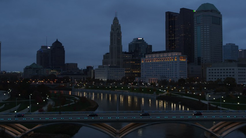 5.7K aerial video descend by the river to reveal bridge, with view of city skyline at twilight in Downtown Columbus, Ohio Aerial Stock Footage | DX0001_002766