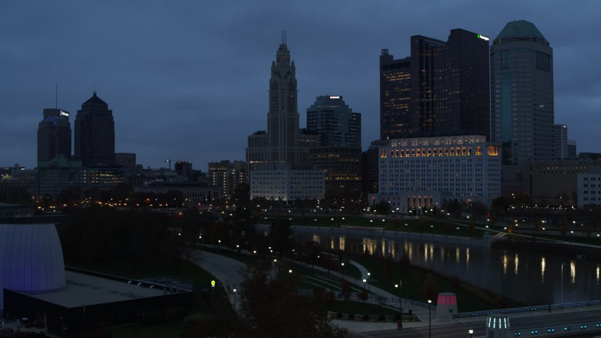 5.7K aerial video ascend by the river with view of city skyline at twilight in Downtown Columbus, Ohio Aerial Stock Footage | DX0001_002767