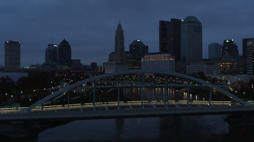 5.7K aerial video flying by bridge with the city skyline in the background at twilight, Downtown Columbus, Ohio Aerial Stock Footage | DX0001_002770