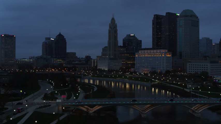 5.7K aerial video flying over bridges to approach the city skyline at twilight, Downtown Columbus, Ohio Aerial Stock Footage | DX0001_002771