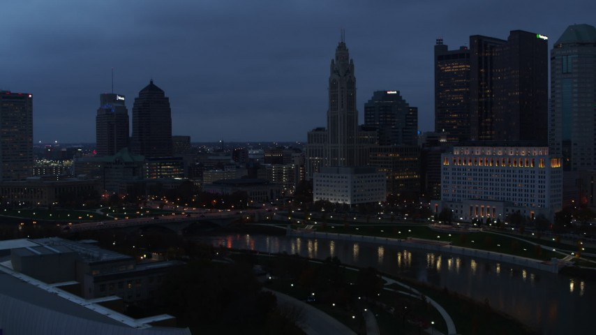 5.7K aerial video of a reverse view of LeVeque Tower across the river at twilight, Downtown Columbus, Ohio Aerial Stock Footage | DX0001_002773