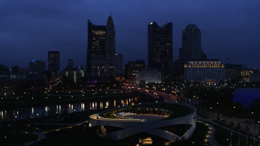 5.7K aerial video of flying by the city skyline across the river at twilight, Downtown Columbus, Ohio Aerial Stock Footage | DX0001_002774