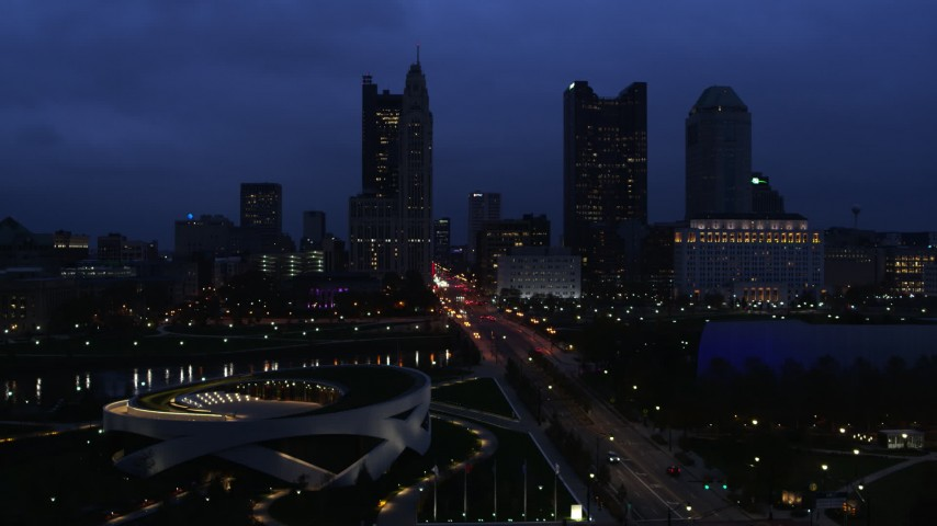 5.7K aerial video of passing by the city skyline across the bridge and river at twilight, Downtown Columbus, Ohio Aerial Stock Footage | DX0001_002775