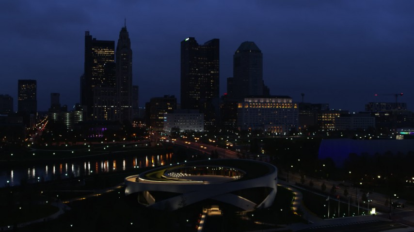 5.7K stock footage aerial video of the city skyline across the bridge and river at twilight during descent, Downtown Columbus, Ohio Aerial Stock Footage | DX0001_002776
