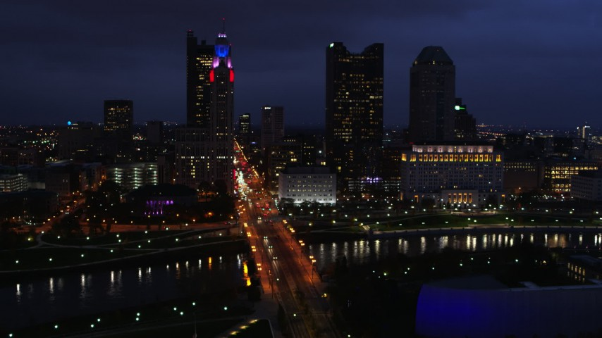 5.7K aerial video of flying by the city's skyline across a bridge and river at twilight, Downtown Columbus, Ohio Aerial Stock Footage | DX0001_002786