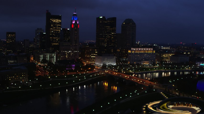 5.7K stock footage aerial video of passing by the city's skyline across a bridge and river at twilight, Downtown Columbus, Ohio Aerial Stock Footage | DX0001_002787