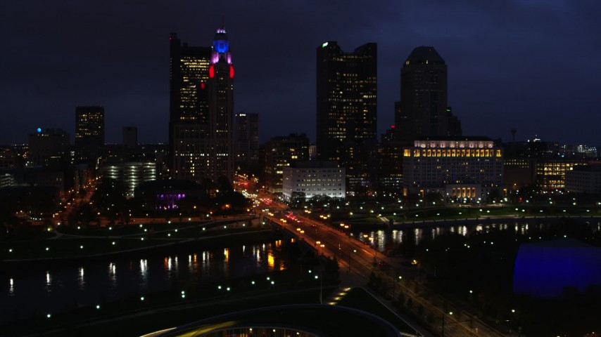 5.7K aerial video of passing a bridge spanning the river and city skyline at twilight, Downtown Columbus, Ohio Aerial Stock Footage DX0001_002791
