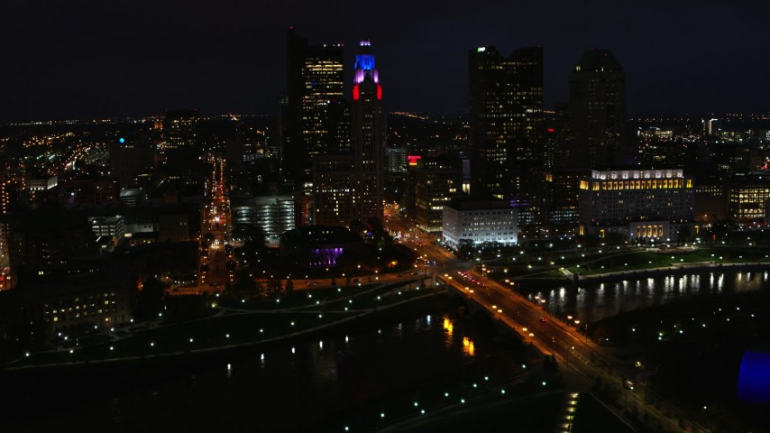 5.7K aerial video of flying by the city skyline, and bridge spanning the river at night, Downtown Columbus, Ohio Aerial Stock Footage | DX0001_002798